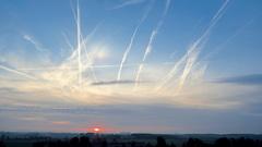 Zonsopkomst achter sluierbewolking, helder blauwe lucht en veel vliegtuigstrepen (07.46) 29-9-2014 Oost Souburg zld. #buienradar